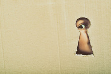 Eye Looking Through A Conceptual Keyhole On Cardboard, Close Up