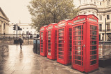 Fototapeta Londyn - Vintage style  red telephone booths on rainy street in London