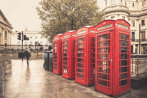 Vintage style  red telephone booths on rainy street in London Poster