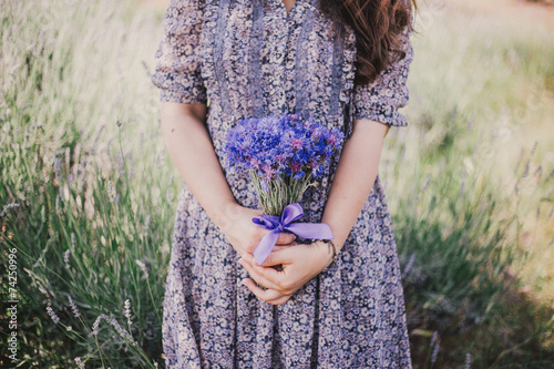 Photo  Woman in blue floral dress with cornflowers in hands