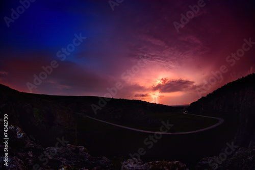 Spoed Fotobehang Onweer Lightening and storm over hills in the night