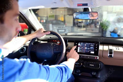 Fotomural  Mann bedient Navigationsgerät im Auto