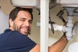 Happy plumber fixing under the sink