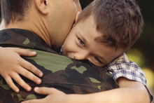 Boy And Soldier In A Military Uniform Say Goodbye Before
