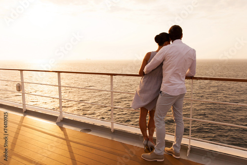 Fotografering young couple hugging at sunset on cruise ship