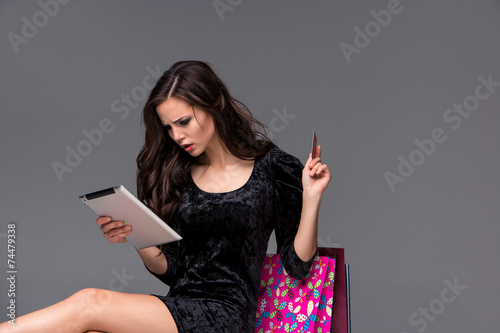 Beautiful young girl paying by credit card for shopping Canvas Print