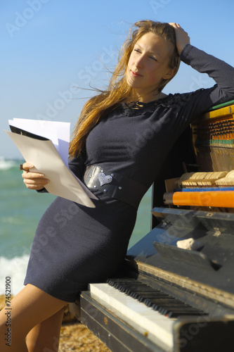 Fotografía beautiful girl with notes from an old piano on the beach