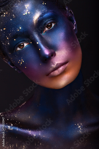 art portrait of a beautiful girl with color paint on her face