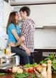 Young loving man and girl having flirt at domestic kitchen