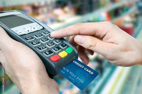 Fotografia  Ręka z kartą kredytową przesuń przez terminal do sprzedaży w superma