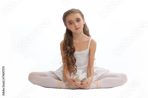 3c4ac4cb8008 young girl in her dance clothes reaching down to touch her foot ...
