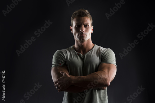 Foto  Handsome muscular young man on dark with stern expression