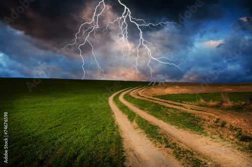 Spoed Fotobehang Onweer Thunderstorm with lightning in green meadow.