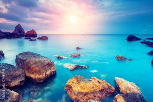 Poster Turquoise Sea stones at sunset