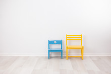Two Vintage Child Chairs On White Wall