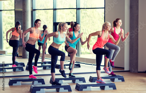 Fototapeta group of women working out with steppers in gym obraz