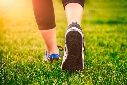 Photo  Girl running shoes closeup, green grass, woman fitness
