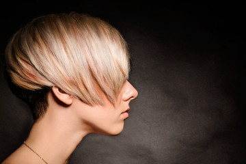 Blonde girl with a short stylish haircut on a dark background