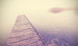 Retro filtered picture of old wooden pier into dense fog.