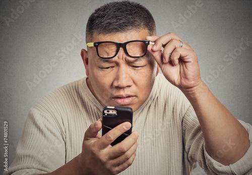 Fotografía  Hombre con gafas que tiene problemas para ver la pantalla del teléfono