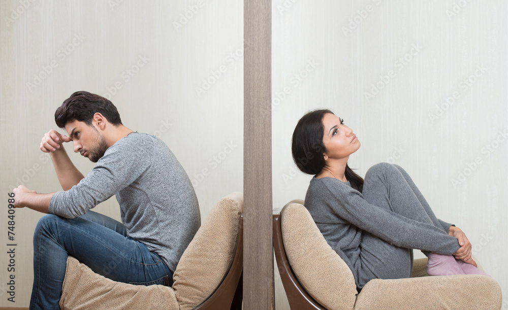 Fototapeta Conflict between man and woman sitting on either side of a wall