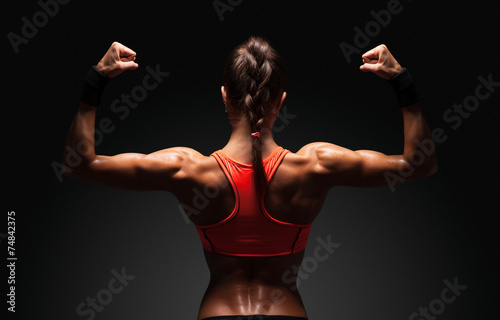 Photo Athletic young woman showing muscles of the back