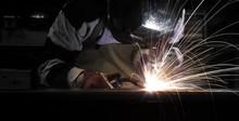 Employee Welding Steel Using MIG/MAG Welder.