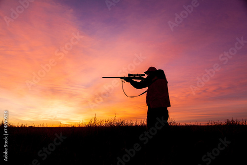 Fotobehang Jacht Rifle hunter Silhouetted at Sunrise