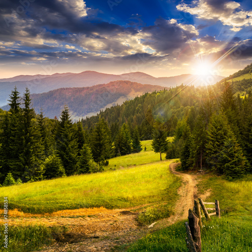 Fototapeta fence on hillside meadow in mountain at sunset obraz