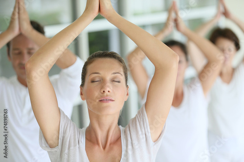 Fotografie, Obraz  Attractive blond woman attending yoga course with group