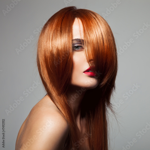 Photo  Beauty model with perfect long glossy red hair. Close-up portrai