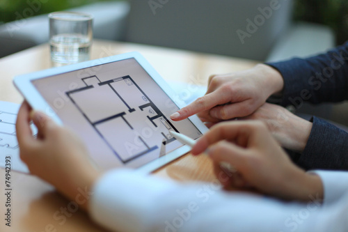 Fotografía  Real-estate agent showing house plans on electronic tablet