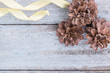 Pine cones and golden ribbon on wood background