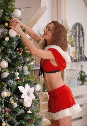 Sexy Santa Claus girl putting Christmas ornaments on the tree Canvas Print