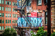 Graffiti And Stairs On The Side Of A Brick Building Seen From Th