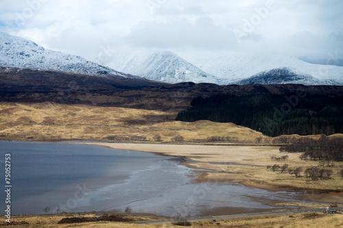Spoed Foto op Canvas Noordzee Strand eines Sees in Schottland mit Gebirge im Hintergrund