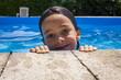 Chica joven descansando sobre el borde de la piscina