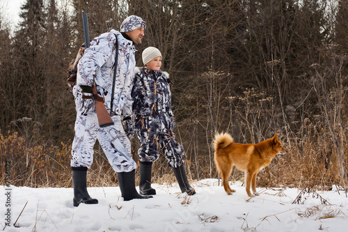 Fotobehang Jacht the hunter with his son and their dog on winter hunting