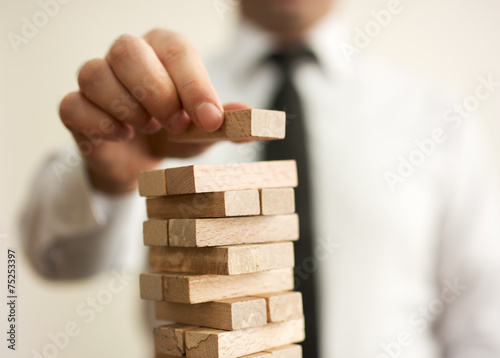 Businessman putting last block to the tower