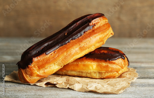 Photographie  Tasty eclairs on wooden table, close up