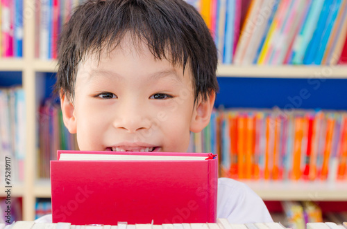 Fotografia  Asian boy student reading book in school library