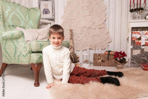 Fototapeta Little boy on carpet in Christmas interior obraz na płótnie