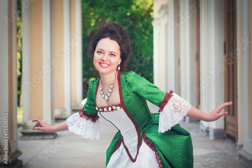 Fotografia, Obraz Beautiful woman in green medieval dress doing curtsey