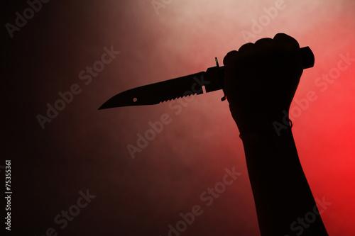 Valokuva Female hand holding knife on red background