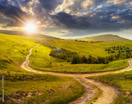 Poster Miel cross road on hillside meadow in mountain at sunrise at sunset