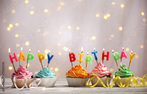 Photo  Delicious birthday cupcakes on table on light background