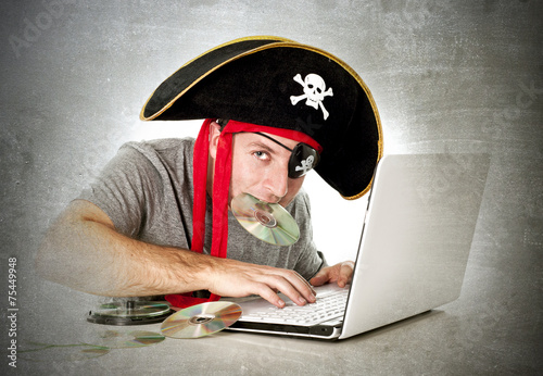 Fotografering  man in pirate hat downloading music files and movies on computer