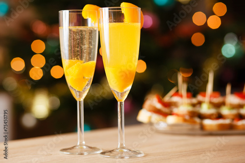 Two glasses of sparkling wine with apricot on the table