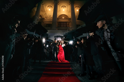 Photo  woman in red dress on the red carpet photos of paparazzi