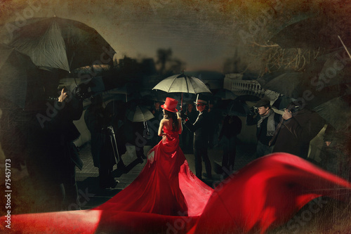 Fotografie, Obraz  Woman in red dress on carpet. photo of paparazzi back.